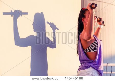 Young woman weights lifting with silhouette background at sunset - Strong fit female body doing workout on terrace with sun light - Concept of healthy lifestyle and body care with soft marsala tones
