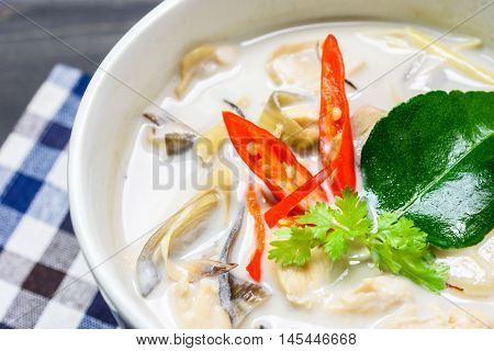 close up coconut milk soup with chicken or Thai chicken coconut Soup ( Tom Kha Gai ) on wooden with table cloth table top view Thai local food