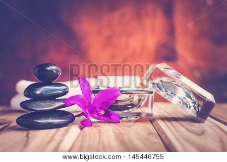 Spa still life black rocks with purple orchids and lotion.