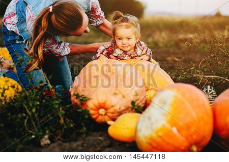 daughter lying on a pumpkin, and her mother standing beside, Halloween eve