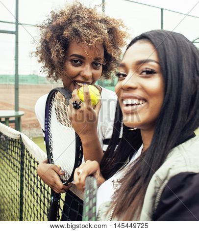 young pretty girlfriends hanging on tennis court, fashion stylish dressed swag, best friends happy smiling together close up