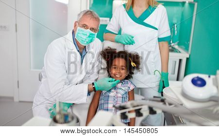 Satisfied black child with dentist after treatment
