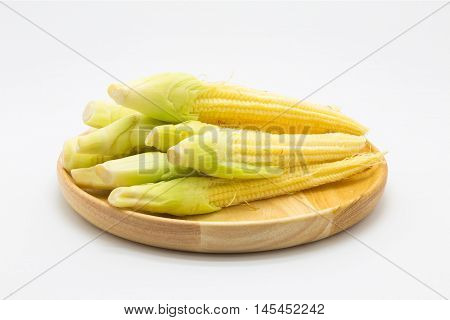 Baby corn on wooden plate, white background
