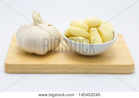 Fresh garlic on wooden board, on white background