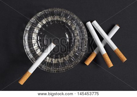 Cigarettes and ashtray on a black background top view