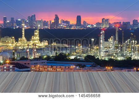 Opening wooden floor, oil refinery with city downtown background, night view
