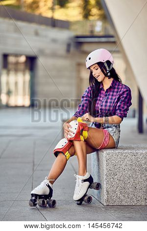 Active lifestyle girl is going to ride on roller skates. Stylish pink skating helmet, knee pads and quad roller skate.