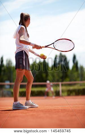 Female tennis player serving ball on tennis court, aside