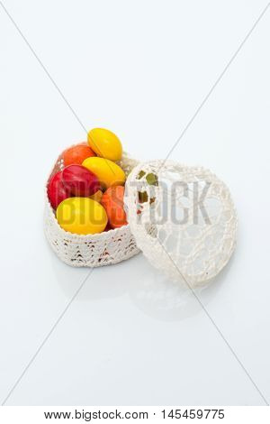 Candy in a casket in the form of heart on a white background