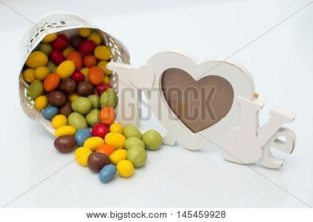 Colorful candy in a pot on a white background near frame