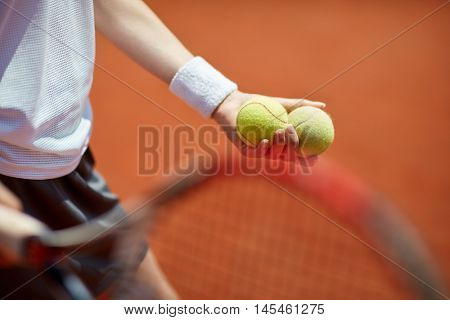 Close up of tennis balls in playerâ??s hand on tennis court