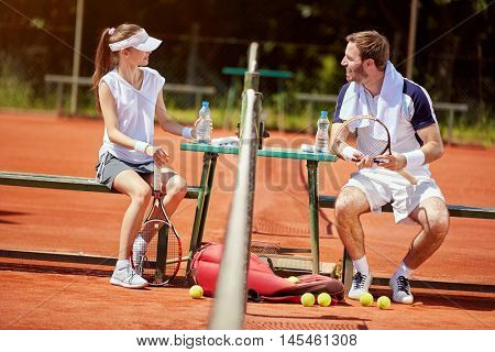 Sportsman and sportswoman resting after tennis training