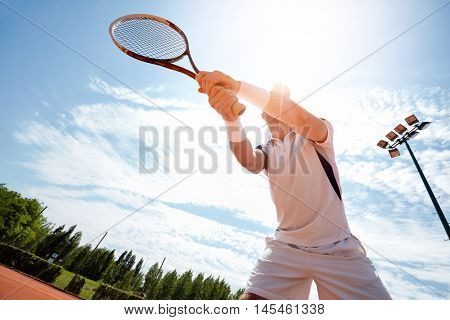 Sportsman on tennis court with racket up in hands