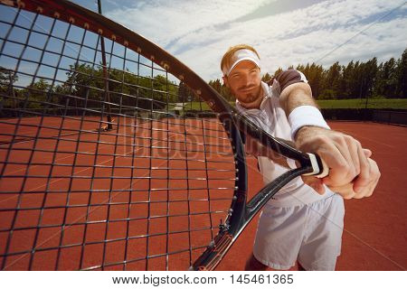 Racket in tennis playerâ??s hand on tennis court