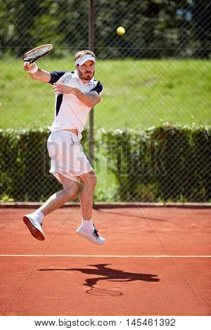 Man serve tennis ball in jump