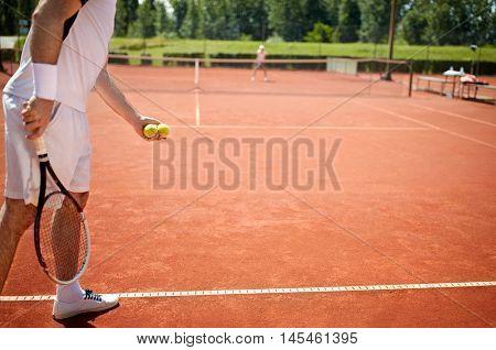 Preparing to serve tennis ball in tennis court