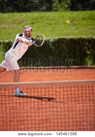 Sportsman vigorously playing tennis in tennis court