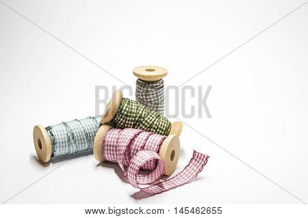 Four spools with checked ribbons on white