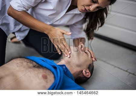 girl assisting an unconscious man after heart attack