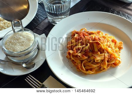 Tagliatelle with tomato sauce and parmesan on a white bowl on a table