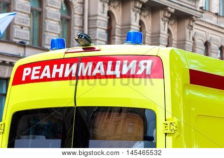 Ambulance car with Blue Flashing Light on the roof. Text in russian: