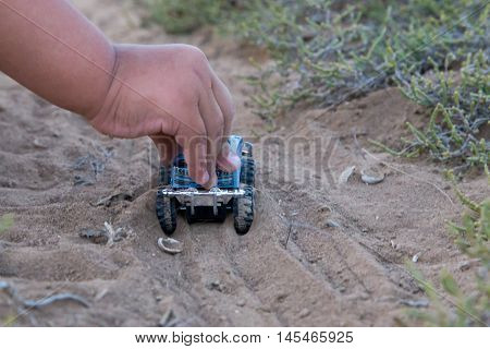 Children's Outdoor Play. The Image Of A Child Who Pushes The Car On The Sand