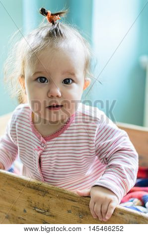 Portrait Of Adorable Little Smiling Baby Girl Staying At Her Bed