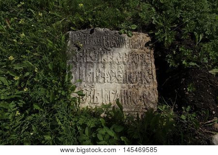 fragment of ancient gravestone inscription in the ancient language close to