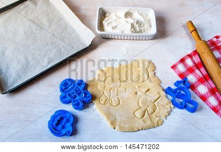 Making cookies for Halloween and Thanksgiving. Fun food for kids, a snack for a party. On a white wooden table cut out shortbread dough, cookie cutters, rolling pin, flour, towel