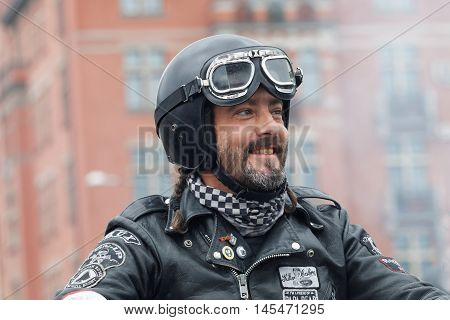 STOCKHOLM SWEDEN - SEPT 03 2016: Closeup of smiling biker wearing leather clothes at the Mods vs Rockers event at the St:Eriks bridge Stockholm Sweden September 03 2016