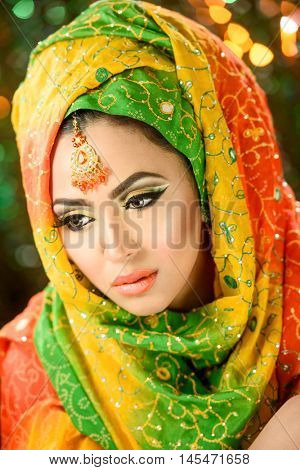 Portrait of a pretty young girl in traditional indian pakistani bridalwear with heavy makeup and jewelry