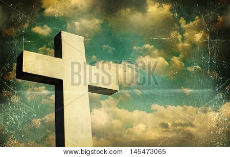 Artistic and vintage image of a Crucifix in the background a beautiful sky