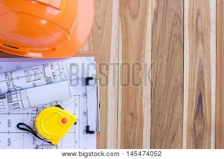 Safety helmet and tape measure over a construction plan drawing for the project engineer jobs