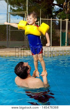 A father holds his son up above the pool water. The boy poses in a super hero type pose.