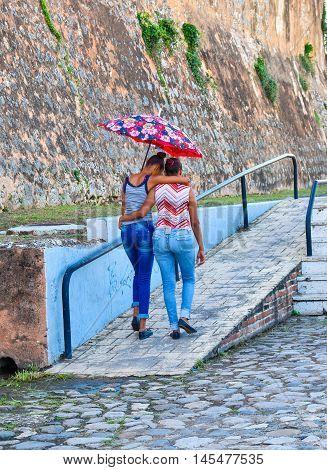 SANTO DOMINGO, DOMINICAN REPUBLIC - JANUARY 29: two girls take shelter from the sun walking with an umbrella on January 29 2016 near Alcazar de Colon, Santo Domingo, Dominican Republic.