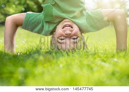Young boy doing a headstand on the grass in the summer sunshine