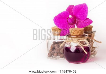 Aromatic oil for Spa in a glass vial surrounded by flowers pink orchid. Spa concept. White background. Copy space