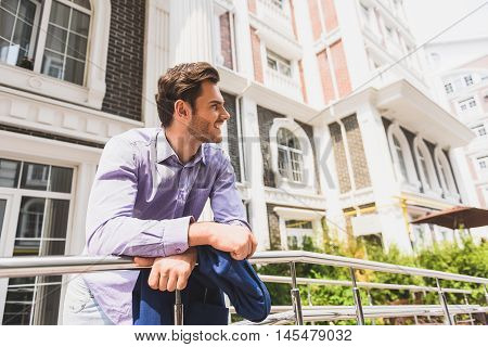 Relaxed young man is breathing fresh air outdoors with enjoyment. He is standing on balcony and looking at city with pleasure. Guy is dreaming and smiling