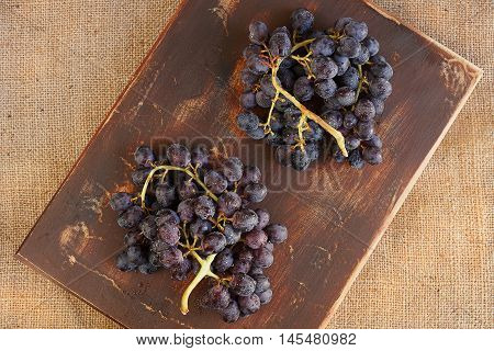 Two bunches of grapes on a brown cutting board. Waterdrops on them.