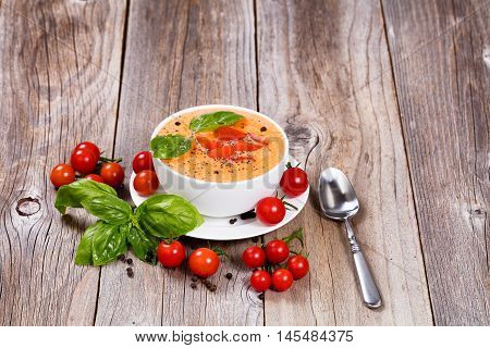 Front view of a fresh bowl of creamy tomato soup with cherry tomatoes and basil on rustic wooden boards.