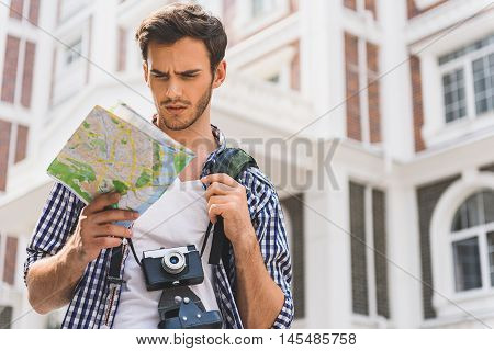 Young male tourist is lost in big city. He is reading map with seriousness. Man is standing on street with backpack