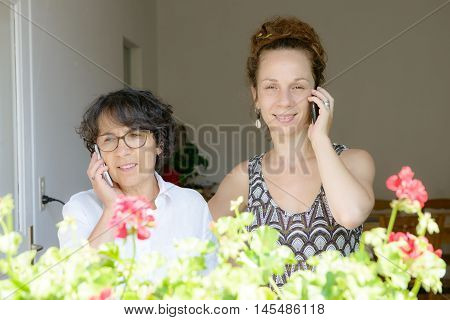 a mother and daughter on the phone in home