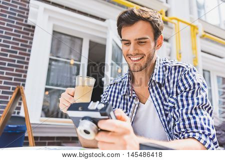 Joyful male tourist is holding camera and looking at shots with curiosity. He is drinking latte and smiling. Man is sitting at table in cafeteria