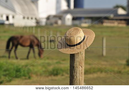 Amish straw hat laying over fence post with Amish farm and horses in background