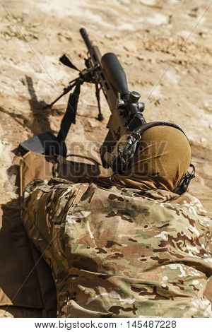 Young male sniper in camouflage with gun in the desert