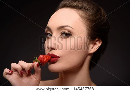 Passionate young woman is kissing red strawberry with temptation. She is standing and looking at camera flirtingly