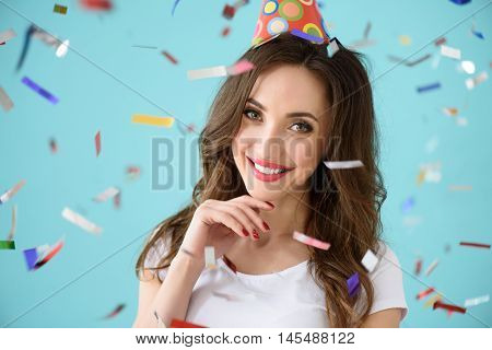 Carefree girl is celebrating her birthday. She is standing and wearing party cone. Lady is smiling. Isolated