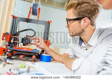 Young man is interested in 3d printer work. He is sitting at table and touching technology with curiosity