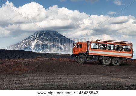 KAMCHATKA RUSSIA - JUNE 24 2016: Russian expedition truck KamAZ (6-wheel drive) on mountain road on background of lava fields and beautiful volcano. Eurasia Russian Federation Far East Kamchatka Peninsula Klyuchevskaya Group of Volcanoes.