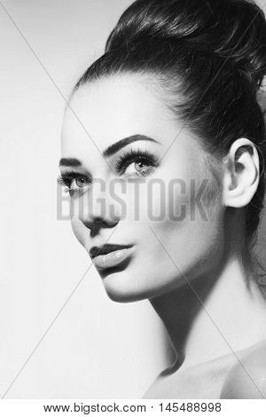 Black and white portrait of young beautiful girl with stylish make-up and hair bun looking upwards, copy space